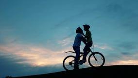 Baiser de jeunes couples romantiques sur des bicyclettes contre le coucher du soleil banque de vidéos