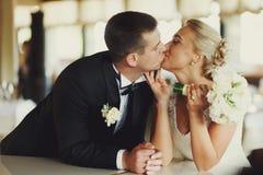 Baiser de jeunes mariés se penchant sur le piano Image stock