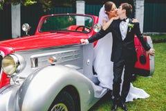 Baiser de jeunes mariés se tenant dans une voiture ouverte de vintage Photos stock