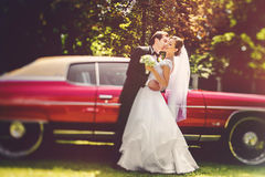 Baiser de jeunes mariés se tenant dans une voiture ouverte de vintage Image libre de droits