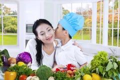 Baiser de petit garçon sa mère dans la cuisine Photographie stock libre de droits
