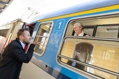 Baiser de soufflement d'homme à la femme sur le train Photographie stock