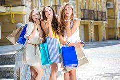 Baiser de trois amies Trois filles tenant les paniers a Photographie stock