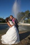 Baiser des jeunes mariés près de la fontaine Photo stock