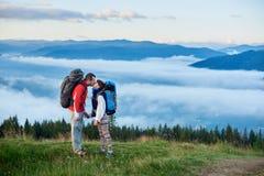 Baiser romantique sur le fond des montagnes puissantes en brouillard sous le ciel avec des nuages Photographie stock