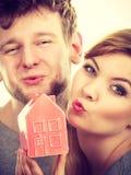 Baisers de part de couples avec le symbole de maison Photographie stock libre de droits