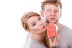 Baisers de part de couples avec le symbole de maison Image stock
