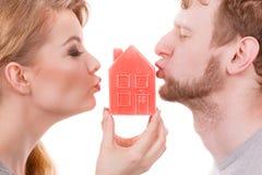 Baisers de part de couples avec le symbole de maison Images libres de droits