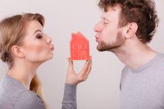 Baisers de part de couples avec le symbole de maison Photos stock