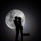 Baisers des amoureux par nuit avec la lune Photographie stock