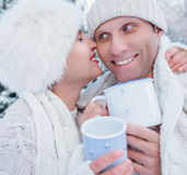Baisers des couples dans l'amour dans la robe confortable avec la tasse de thé chaud Image libre de droits