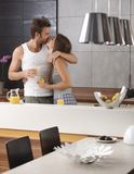 Baisers des couples dans la cuisine pendant le matin Images stock