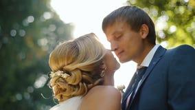 Baisers des couples de mariage dans les sunlits lumineux Les nouveaux mariés adorables frottent tendrement des nez en parc banque de vidéos