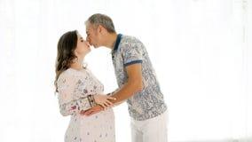 Baisers des couples heureux attendant le bébé images stock
