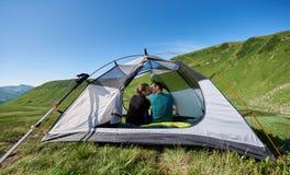 Baisers doux de couples dans la tente des vacances actives d'été aux montagnes carpathiennes Photographie stock