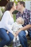 Baisers enceintes heureux de couples comme montres de bébé Images stock
