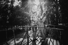 Baisers et support romantiques de couples de photographie blanche noire jeunes au pont sur le fond Photographie stock