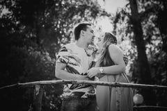 Baisers et support romantiques de couples de photographie blanche noire jeunes au pont sur le fond Image libre de droits