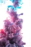 Baisse d'encre de couleur dans l'eau violette rougeâtre, profondément bleu, scintillement, cyan Photos stock