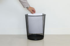 Baisse d'homme d'affaires un papier inutile dedans aux déchets Photos libres de droits