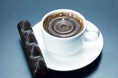 Baisse de lait tombant dans une tasse blanche avec du caf? noir photographie stock