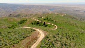 Baisse de vue aérienne dans l'altitude au-dessus d'une route d'enroulement faite de saleté en Idaho banque de vidéos