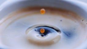 Baisse des chutes de café dans la tasse remplie banque de vidéos