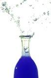 Baisses bleues tirant hors de la bouteille photographie stock