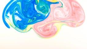 Baisses colorées de peinture se mélangeant dans le lait Modèles colorés de peinture liquide de la surface en mouvement images libres de droits