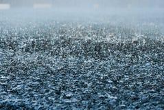 Baisses de forte pluie sur la route goudronnée photographie stock libre de droits