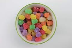 Baisses de gomme de sucrerie dans un bol en verre vert et blanc d?coratif sur un fond blanc d'isolement images stock