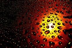 Baisses de l'eau avec le fond rougeoyant Images stock