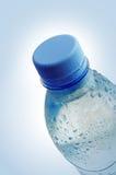 Baisses de l'eau sur une bouteille en plastique images stock