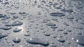 Baisses de l'eau sur une finition métallique brillante gris-clair image stock