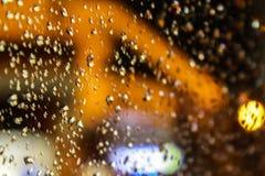 Baisses de l'eau sur une surface en verre transparente avec le fond brouillé de bokeh images stock