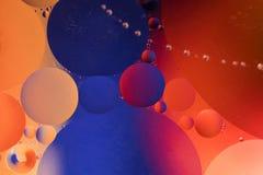 Baisses de pétrole dans l'eau sur un fond coloré Photos stock