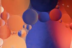 Baisses de pétrole dans l'eau sur un fond coloré Image libre de droits