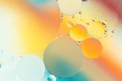 Baisses de pétrole dans l'eau sur un fond coloré Photo stock