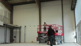 Baisses de plate-forme de levage de ciseaux hydrauliques dans un entrepôt banque de vidéos