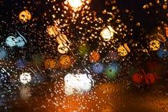 Baisses de pluie sur l'hublot Ville de nuit de Bokeh Photographie stock libre de droits