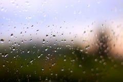 Baisses de pluie sur la fenêtre avec le coucher du soleil derrière photos libres de droits