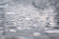 Baisses de pluie sur la table en verre Photos stock