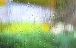 Baisses de pluie sur le verre de fenêtre avec le fond jaune et vert Photos libres de droits