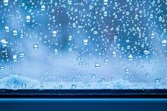 Baisses de pluie sur le verre et de neige près de la fenêtre Temps pluvieux dans le winter_ photos stock