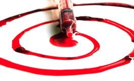 Baisses de sang et de seringues au milieu Photographie stock libre de droits