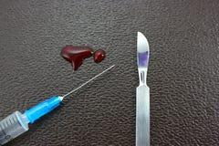 Baisses de seringue de sang sur un fond foncé Images libres de droits