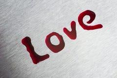 Baisses rouges sous forme d'amour de mot La surface est métallique Photos libres de droits