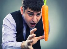 Bait metaphor. Man and carrot Royalty Free Stock Photo