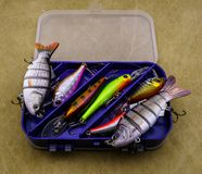 Baits for fishing on canvas background. Several wobblers of different colors in the box for fishing gear. Baits for fishing on canvas background. Several stock images