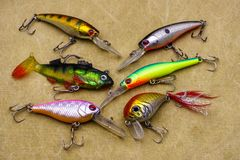 Baits for fishing on canvas background. Several wobblers of different colors. Baits for fishing on canvas background. Wobblers of different colors stock images